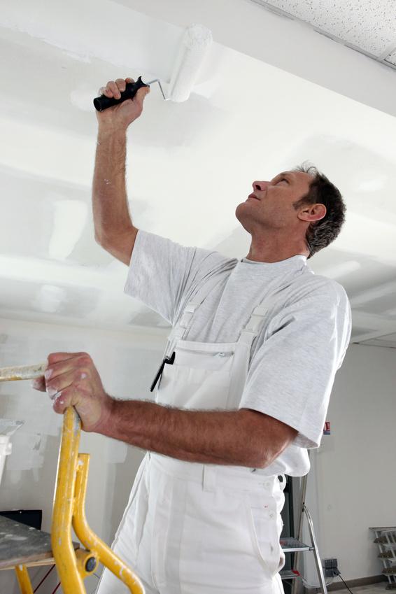 Homme peignant un plafond en blanc